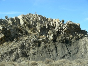 An sill of andesite capping tilted layers of Mancos Shale in the Cerrillos Hills