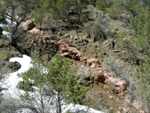 A dike of coarse, pink granite cutting through darker rocks in the mountains near Santa Fe
